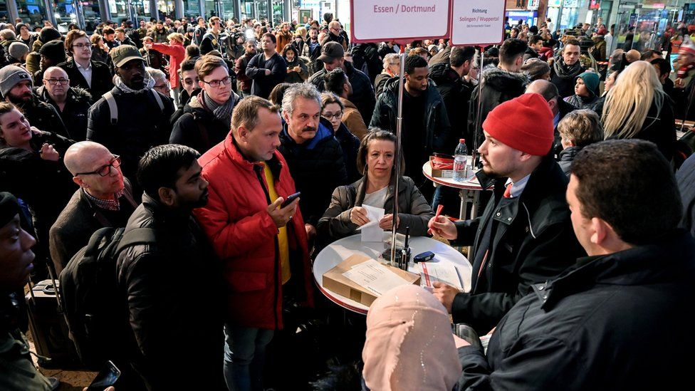 Passengers look at display boards and try to get delay information from German railway company Deutsche Bahn (DB) employees during a passing nationwide storm, at Cologne central railway station, Germany, 9 February 2020