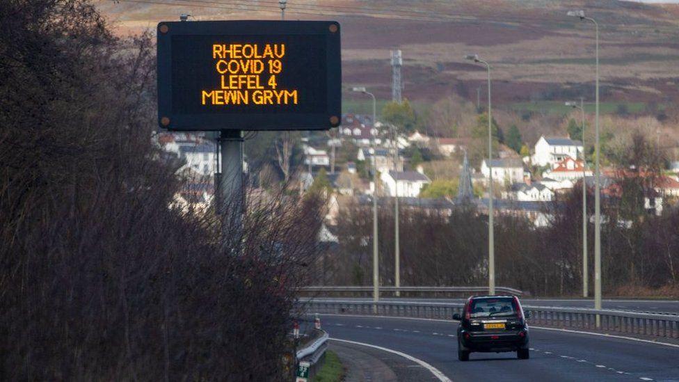 """Merthyr road with sign in Welsh """"Rheolau Covid 19 Lefel 4 Mewn Grym"""" - 'Covid 19 Rules - Level 4 in force'"""