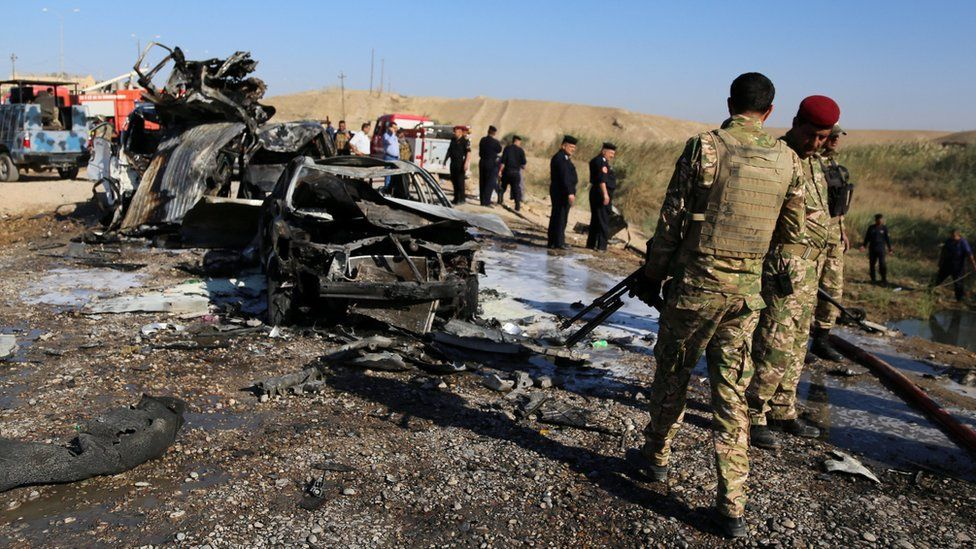 Iraqi forces inspect the site of a suicide bomb attack near Tikrit on 6 November 2016