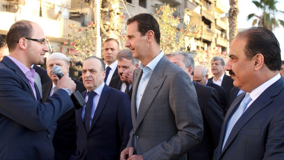 Syrian President Bashar al-Assad speaks to a reporter during a tour of the Damascus suburb of Darayya (12 September 2016)