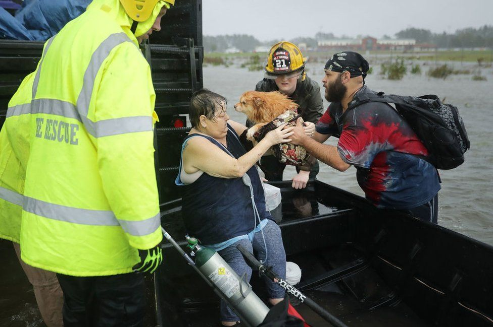 A woman and her dog being rescued