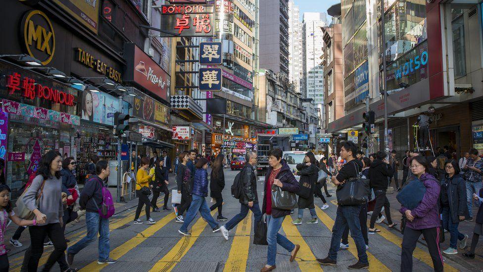 Pedestrians cross a street in Causeway Bay, Hong Kong