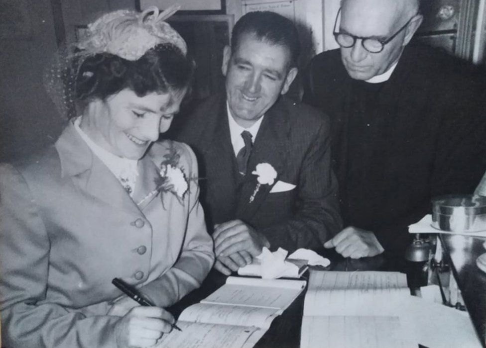 Bridget Dolan signing the marriage register on her wedding day