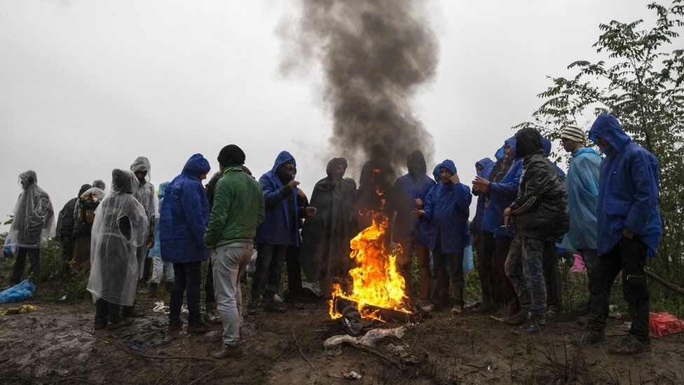 Migrants gather around a bonfire as they wait to cross the border with Croatia near the village of Berkasovo, Serbia, October 19, 2015.