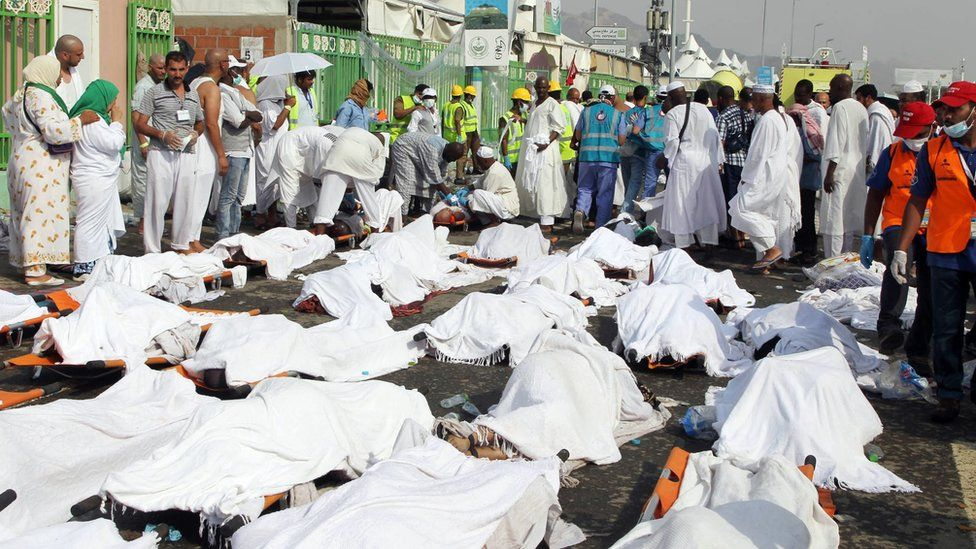 Saudi emergency personnel stand near bodies of Hajj pilgrims at the site where at least 717 were killed and hundreds wounded in a stampede in Mina
