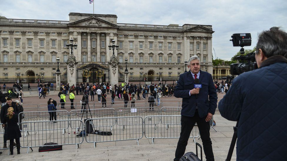 A news broadcaster speaks to camera as members of the public queue to read the official notice of the birth of a baby boy to the Duke and Duchess of Sussex outside Buckingham Palace on May 6, 2019