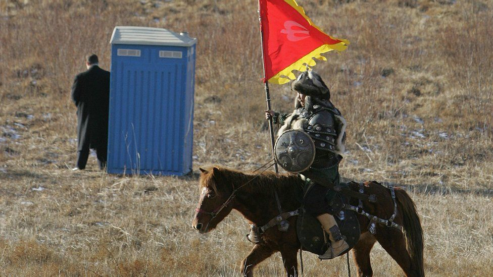 An actor dressed as a Mongolian warrior rides his horse past a US Secret Service Agent standing next to a portable toilet