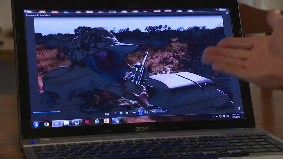 activist points to computer screen displaying footage of hunter in a jeep