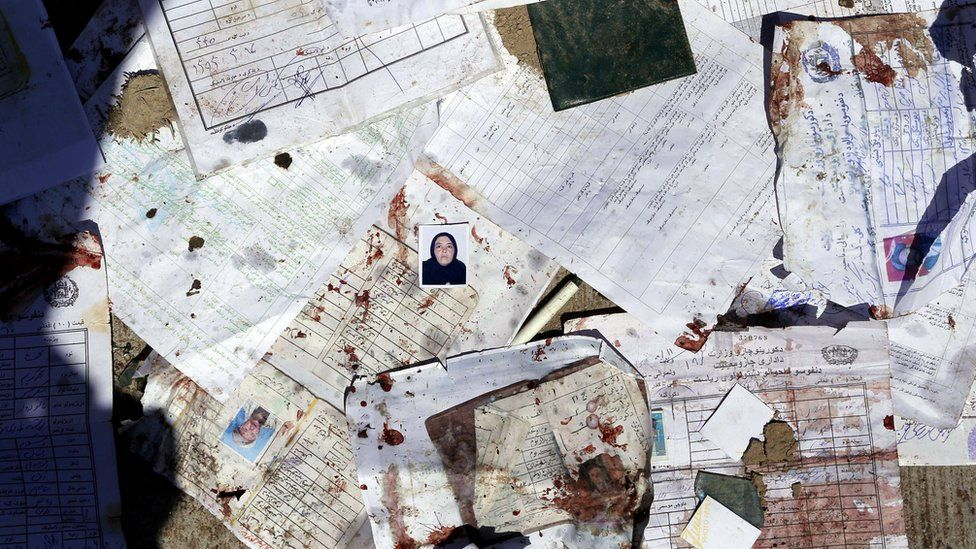 Passport photos and forms lie in the street after the bomb attack in Kabul, 22 April
