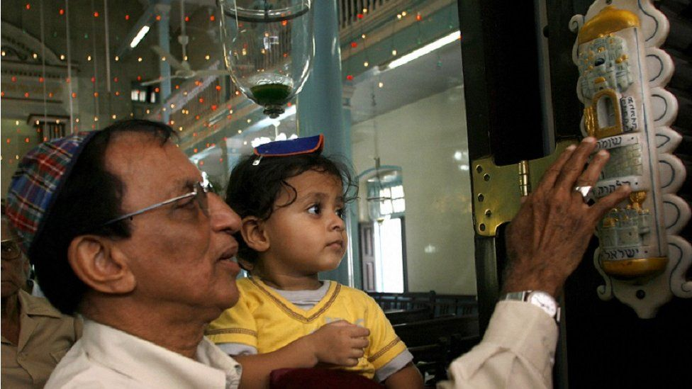 Indian Jewish man with his child touching the mezuzah at synagogue