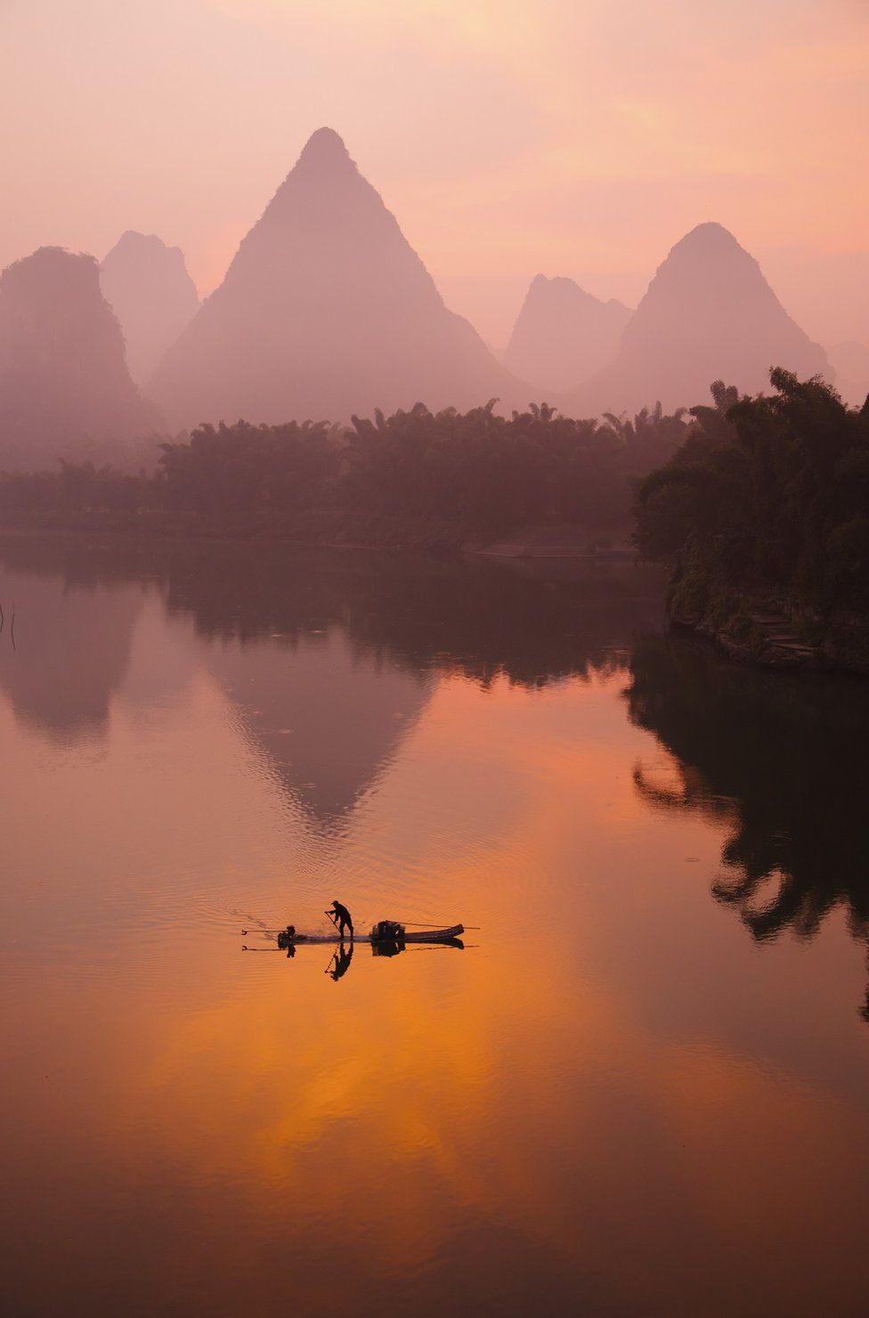 A sunset view of a person on a boat on water with mountains behind them