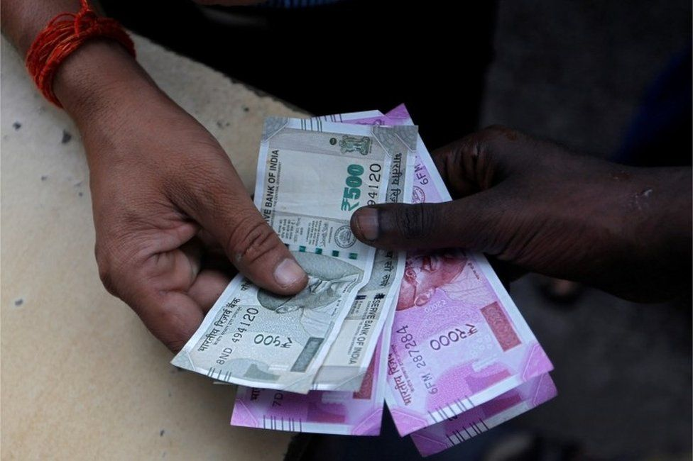 A customer hands Indian currency notes to an attendant at a fuel station in Mumbai, India, August 13, 2018. REUTERS/Francis Mascarenhas