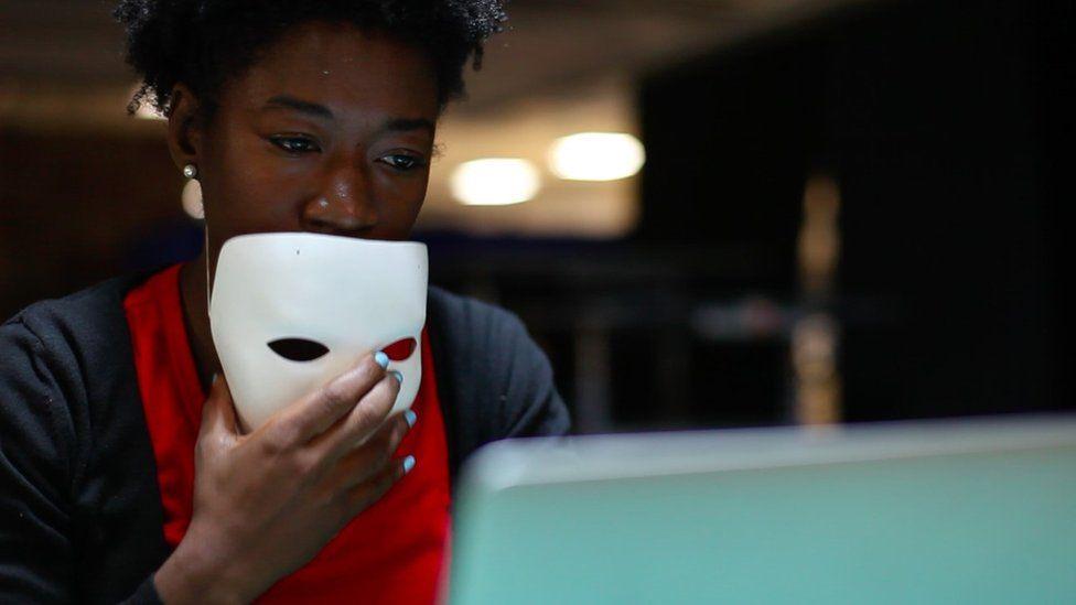 Joy Buolamwini holding a white mask at a computer
