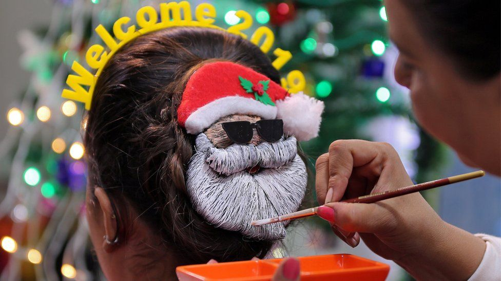 A make-up artist decorates the hair of a woman in the shape of Santa Claus during the New Year preparations in Ahmedabad, India, 31 December 2018