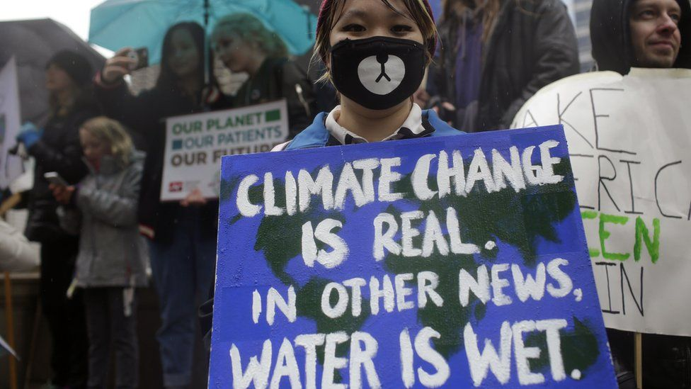 Demonstrators holds signs during the People's Climate March outside Trump International Hotel & Tower on April 29, 2017 in Chicago, Illinois.