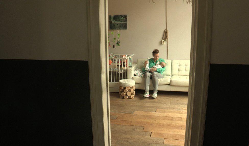 Babs holding baby Yoeki on sofa