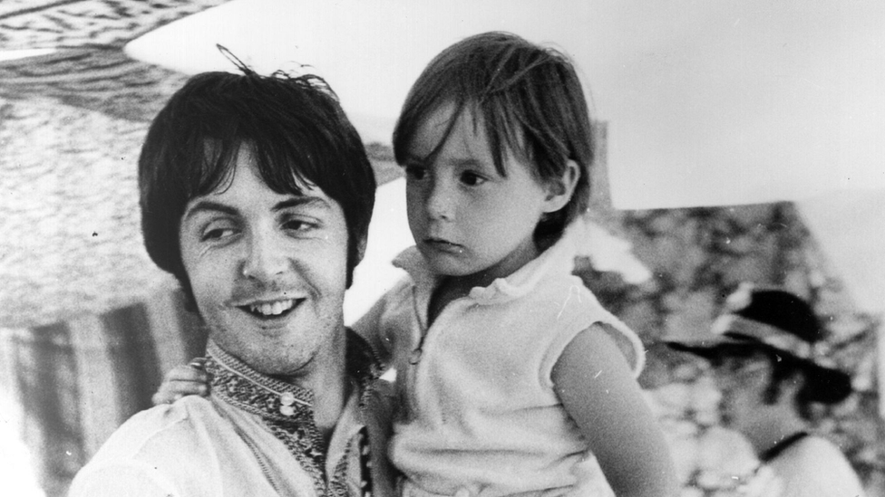 Paul McCartney holds four year old Julian, son of his colleague John Lennon (visible in the background) during a holiday