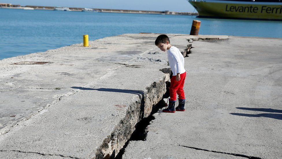Child peers at damaged pier at port on Zakynthos