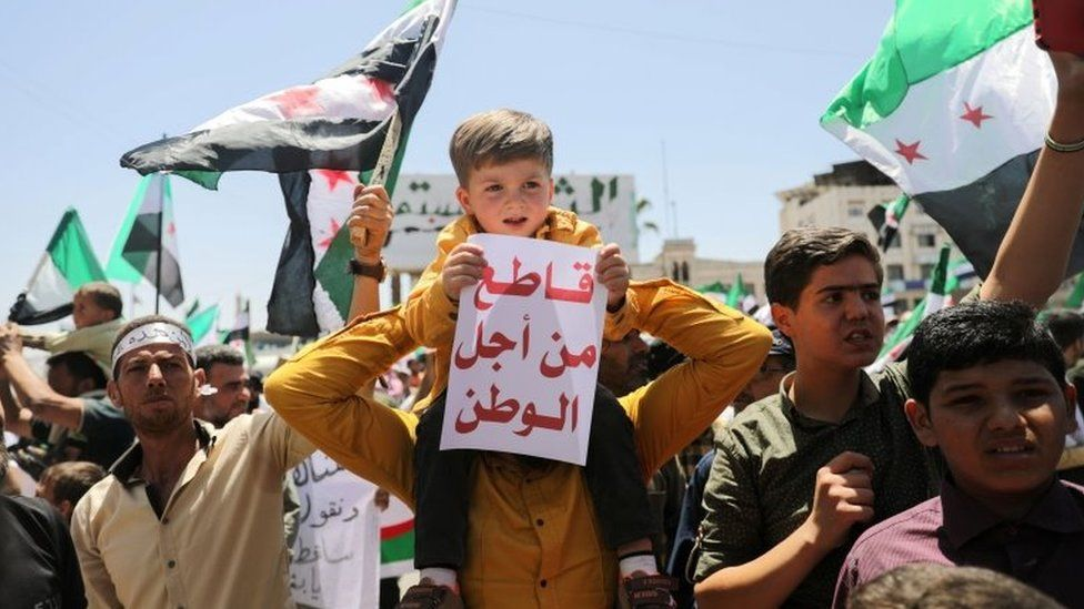 """A boy, carried on the shoulders of a man, holds a sign reading """"boycott for the sake of home"""" during a protest against the presidential election in opposition-held Idlib province (26 May 2021)"""