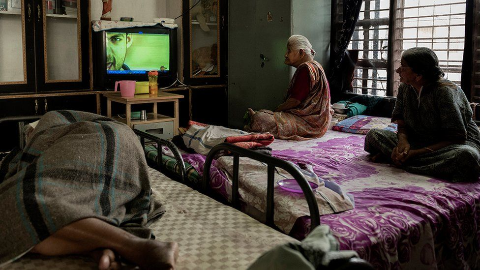Two old women watching TV while an older person sleeps on a bed near them