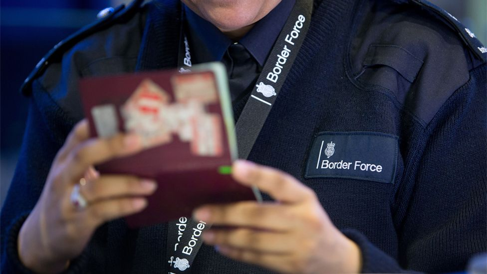 A UK Border Force officer checking a passport in Terminal 2 of London's Heathrow Airport