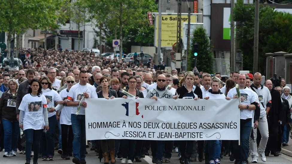 People and policemen take part in a march from Mantes-la-Jolie, western suburbs of Paris, on June 16, 2016, in tribute to French policeman Jean-Baptiste Salvaing and his partner Jessica Schneider killed outside their home in the Paris suburb of Magnanville.