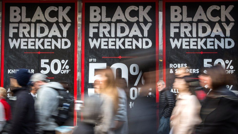 People walk past a shopfront on Oxford Street advertising 'Black Friday' discounts.