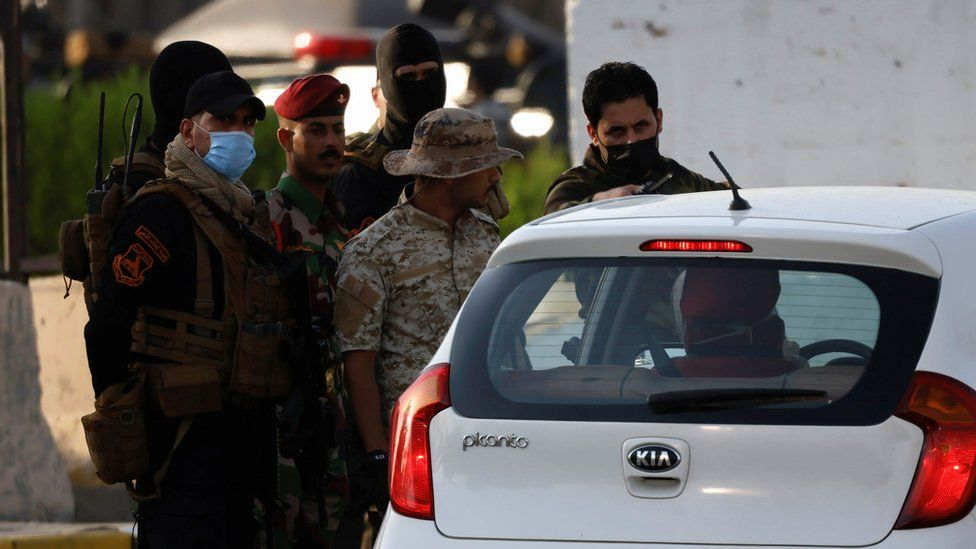 Popular Mobilisation Forces inspect a vehicle at an entrance to Baghdad's Green Zone on 26 May 2021