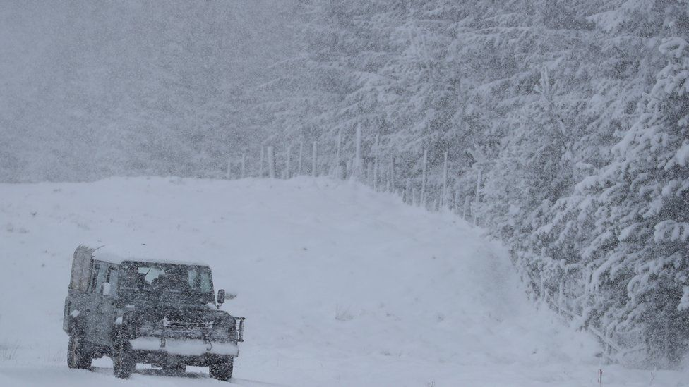 A Land Rover drives on a snow-covered road near Trinafour, Scotland.