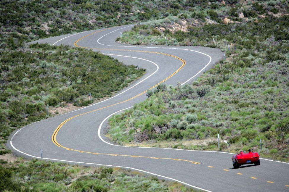A bright red convertible sports car up a winding road