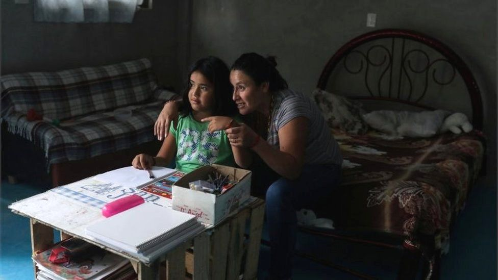 Karina Fuentes helps her daughter Julieta, 7, during a televised class as millions of students returned to classes virtually after schools were ordered into lockdown in March, due to the coronavirus disease (COVID-19) outbreak, in Chilcuautla, Hildalgo state, Mexico August 24, 2020.