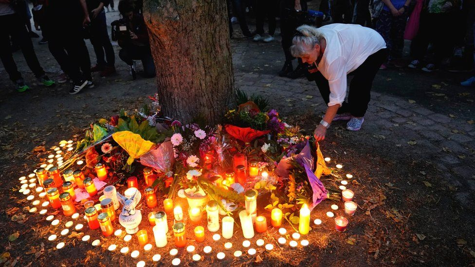 A woman lights a candle after a mourning march for a 22-year-old man killed in Köthen, Germany, 9 September 2018