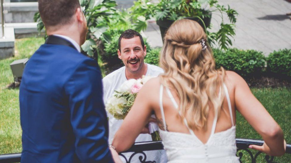 The couple in their wedding attire look over a balcony to talk to Adam Sandler.