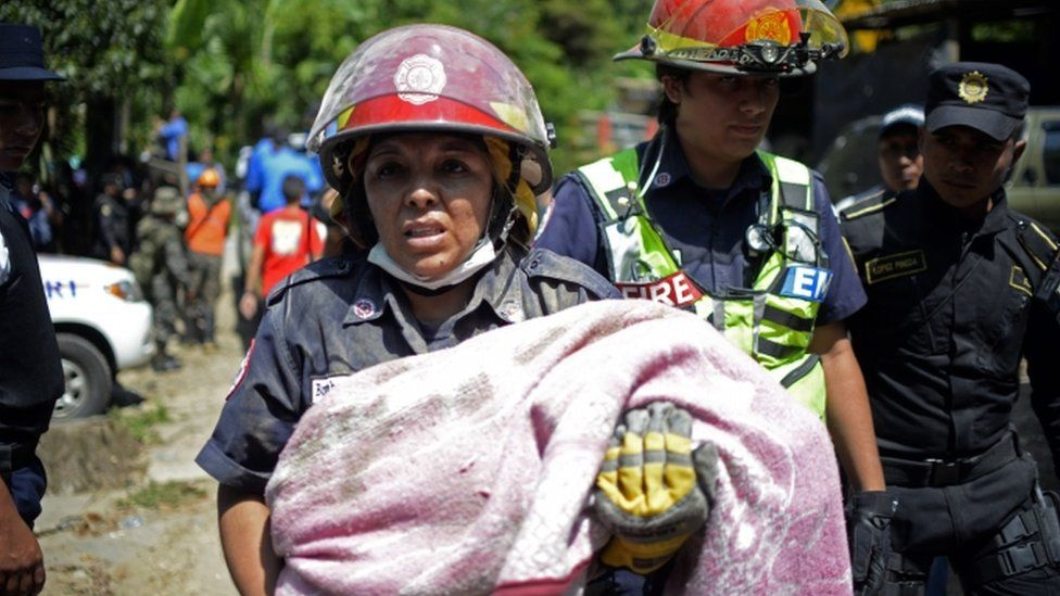 Rescuers carry a children victim of a landslide at Cambray village, in Santa Catarina Pinula municipality, Guatemala on October 2, 2015.