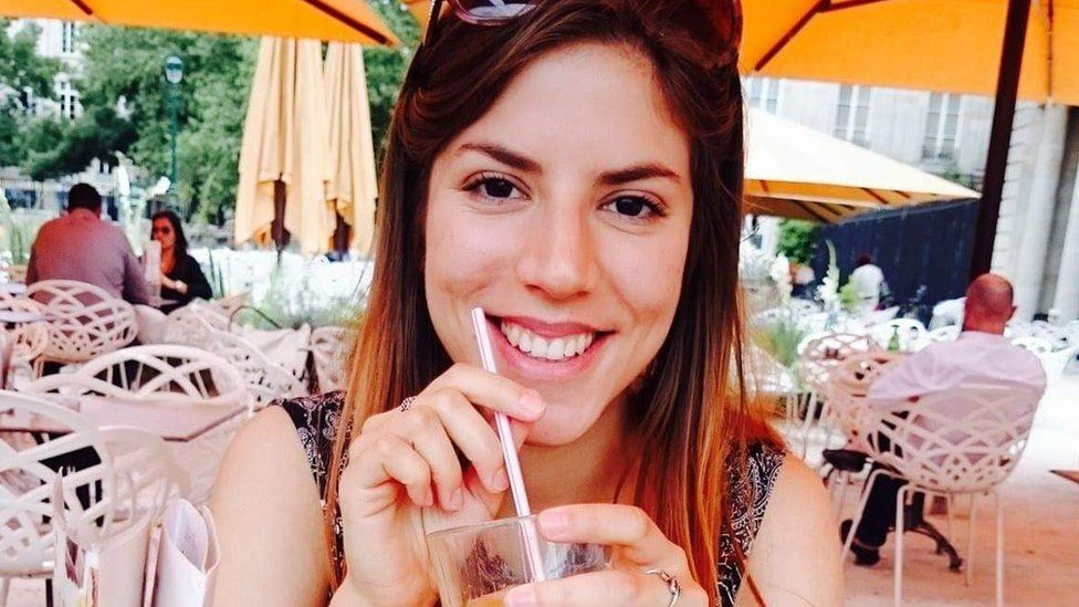 Nadza Dzinalija is pictured in a restaurant, smiling at the camera