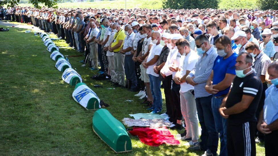 People pray near coffins at a graveyard during a mass funeral in Potocari