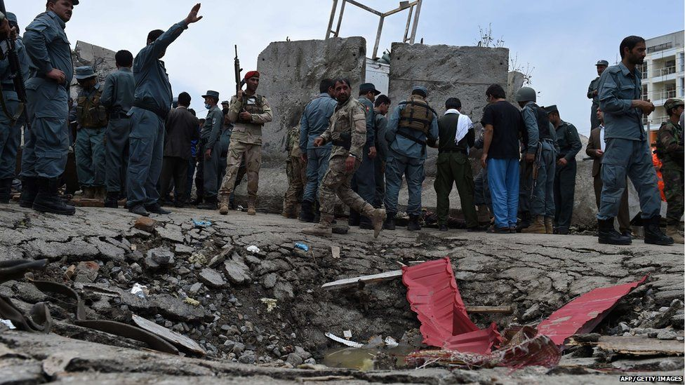 Afghan security personnel stand at the scene of a suicide attack by Taliban militants on the Afghan parliament building in Kabul on June 22, 2015.