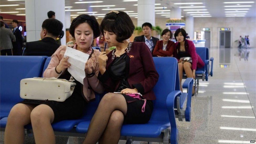 Women sitting at Pyongyang's international airport, 8 October 2015