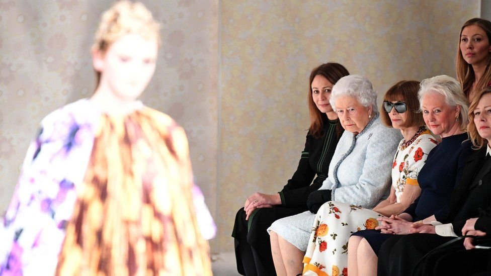 The Queen and Anna Wintour watch as a model walks the runway