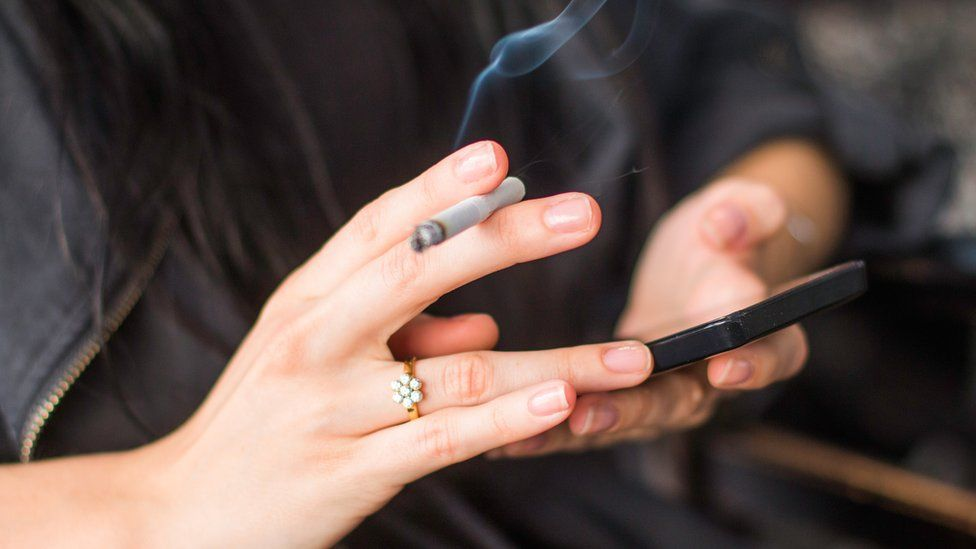 hands holding a cigarette and a smartphone