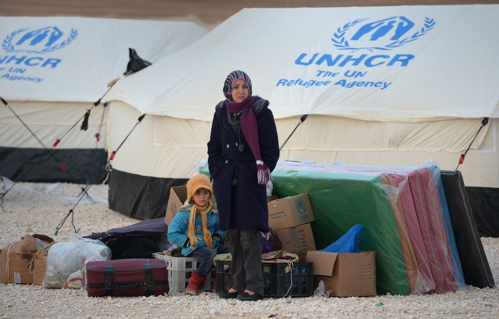 Refugees stand with a few possessions in a refugee camp in Jordan