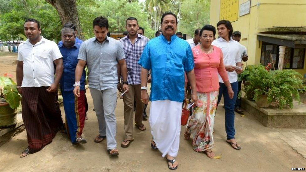 Former President Mahinda Rajapaksa (third on the right) arrives at a polling station during the general election in Medamulana (17 August 2015)