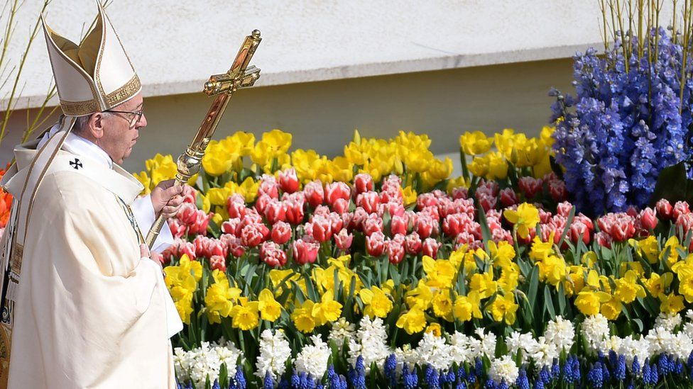Pope Francis walks past flowers adorning the altar during the Easter Sunday mass on April 16, 2017 at St Peter's square in Vatican.