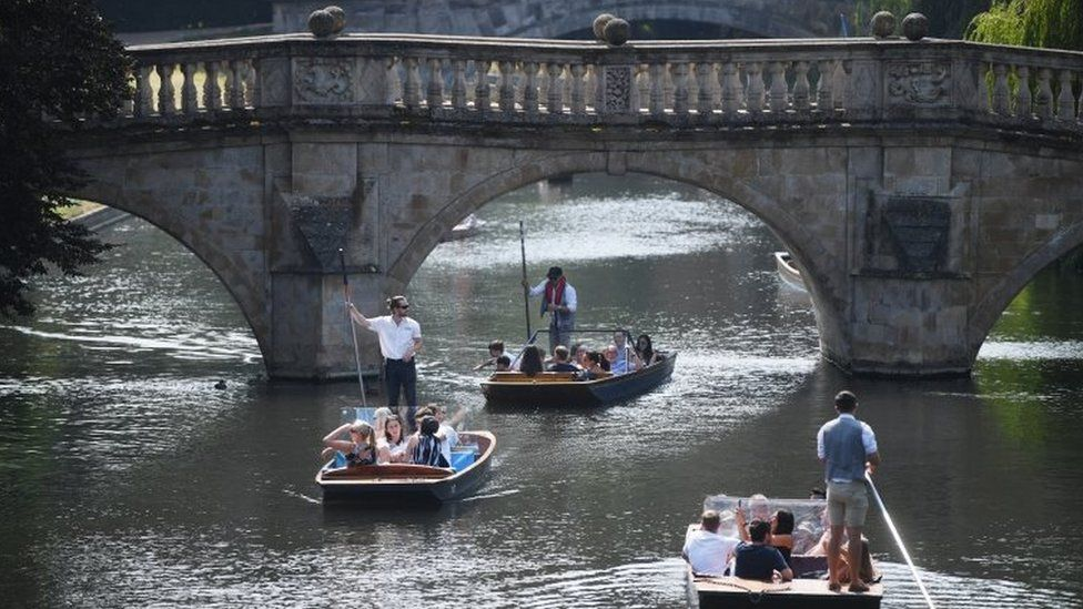 People punt along the river Cam on a hot day in Cambridge