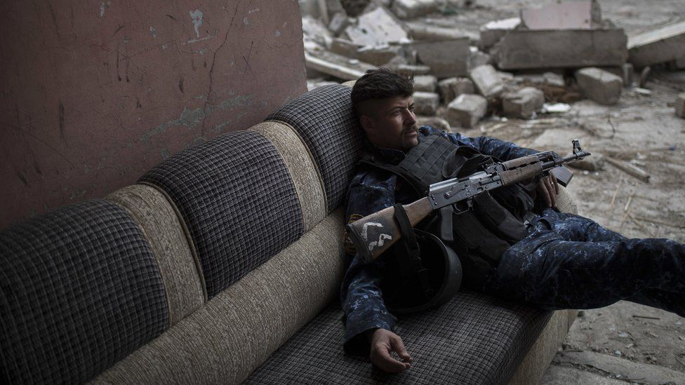 A Federal Police soldier lays on a couch before moving to a front line near the old city during fighting against Islamic State militants on the western side of in Mosul, Iraq, Tuesday, March 28, 2017. (