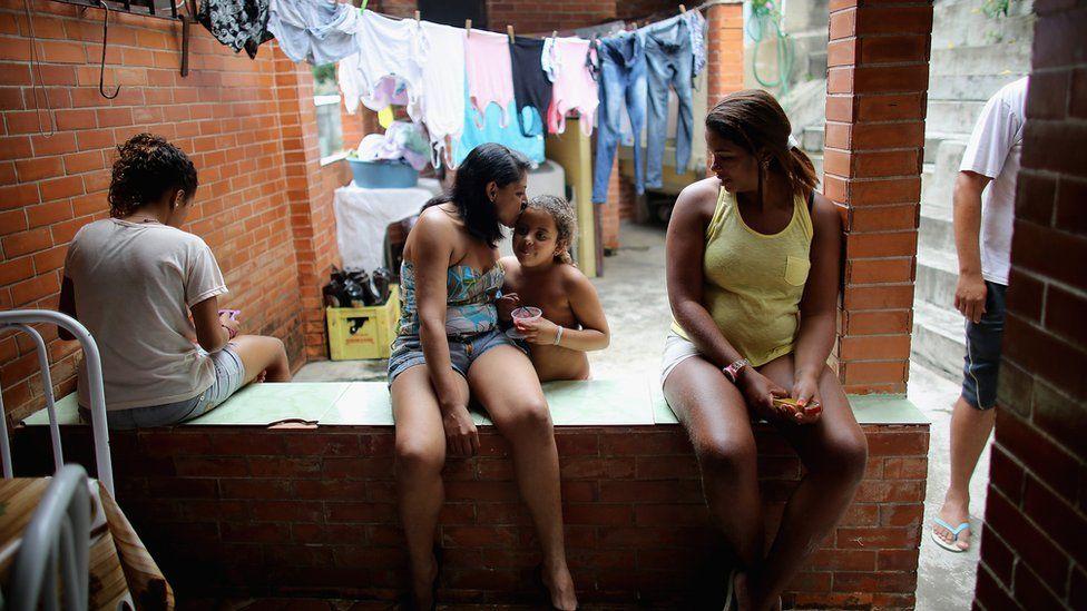 Members of the Das Neves family sit in their home in the Prazeres favela in Rio de Janeiro. The family participates in Brazil's 'Bolsa Familia' programme