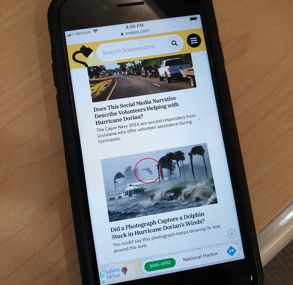 A photograph of the Snopes website on a phone highlight two stories asking about Hurricane Dorian