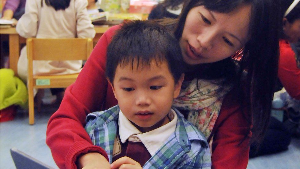 A boy and his mother read a book in the Taipei public library in Taipei on November 18, 2012.