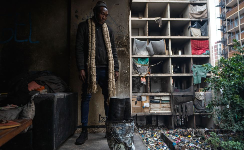 Sabelo Mapempeni stands in one of the rooms looking out of the derelict San Jose building in Johannesburg, South Africa