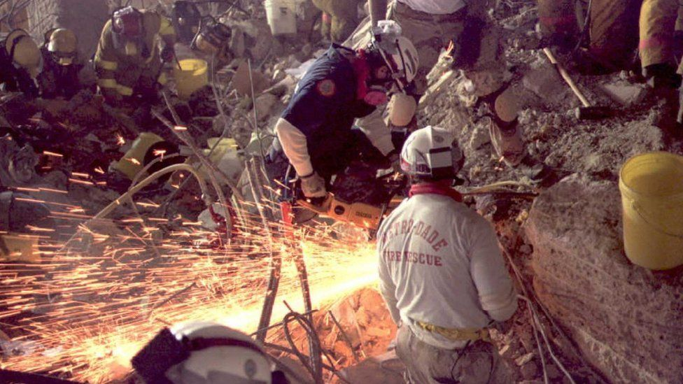 Firefighters use tools to try and blast through remains of building to find victims